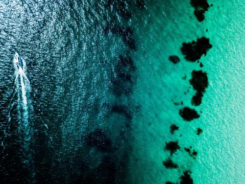 image of the sea from above, a boat on the far left in deeper water leaves a small white wake