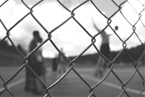 young people playing basketball behind a fence