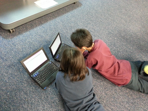 Two primary school aged children, lying on the floor on their bellies, using a laptop each