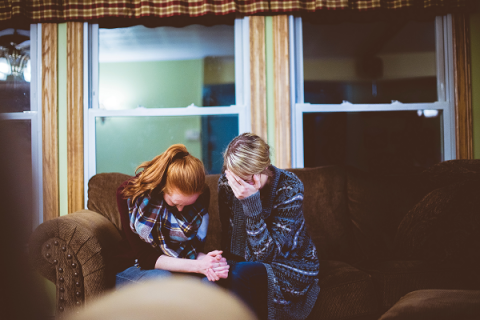 Two women sit with heads bowed on a brown couch